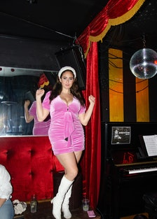 the comedian Catherine Cohen wearing a pink dress on stage at a comedy show