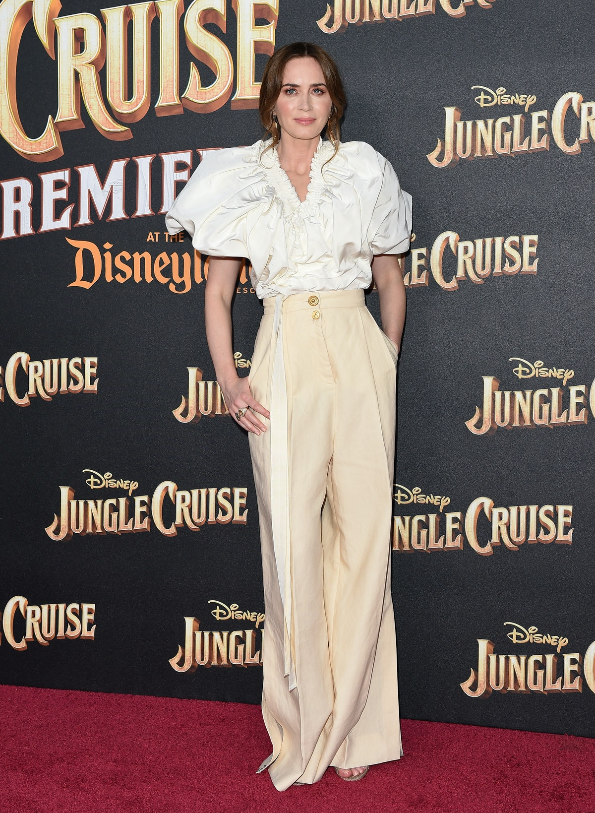 Emily Blunt in a blouse and pants.