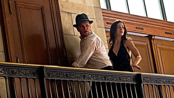 David (Matt Damon), sporting a fedora, is on the run with Elise (Emily Blunt) in The Adjustment Bure...
