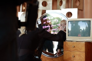 Billie Eilish writes on a mirror at her Spotify-hosted album launch party, 'Happier Than Ever: The D...
