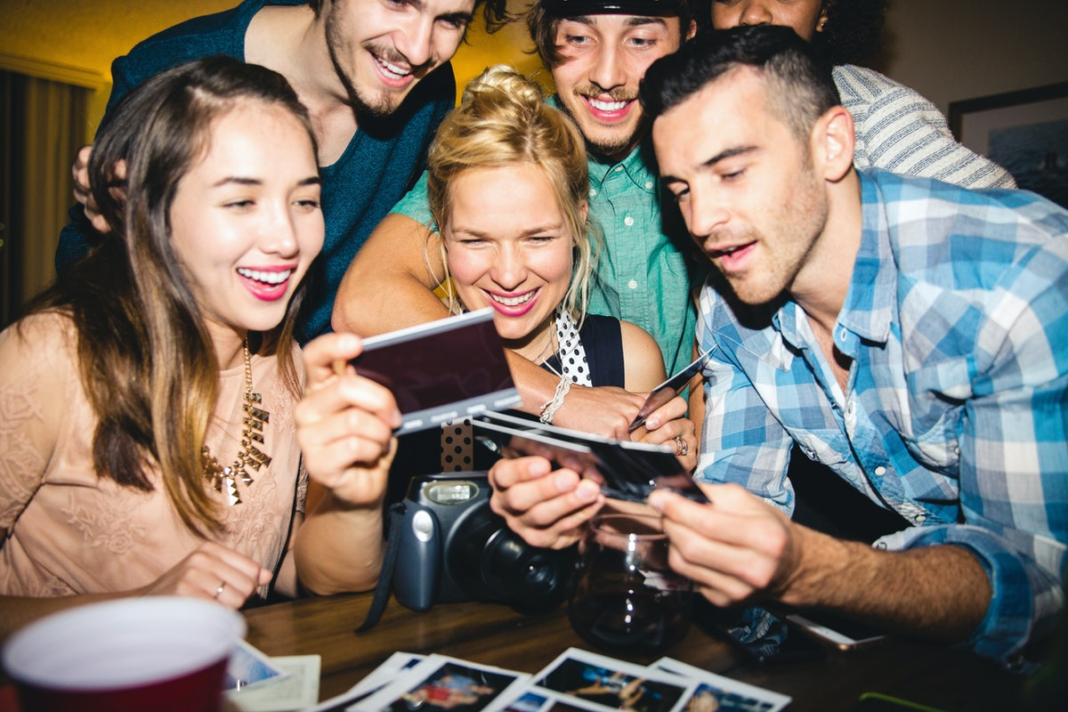 6 friends looking at throwback pictures before posting on Instagram with a clever caption.