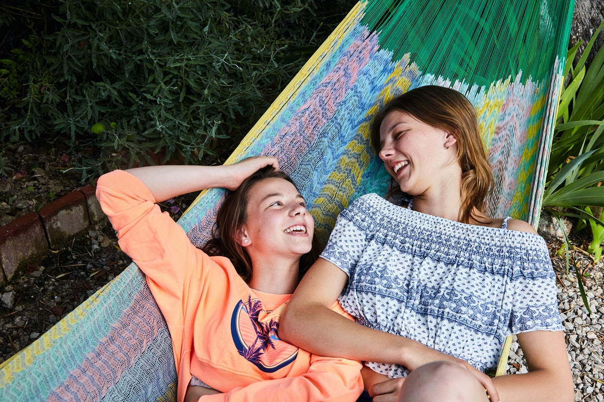 Sisters laying in a hammock to show comments you can post on your little sister's pic.