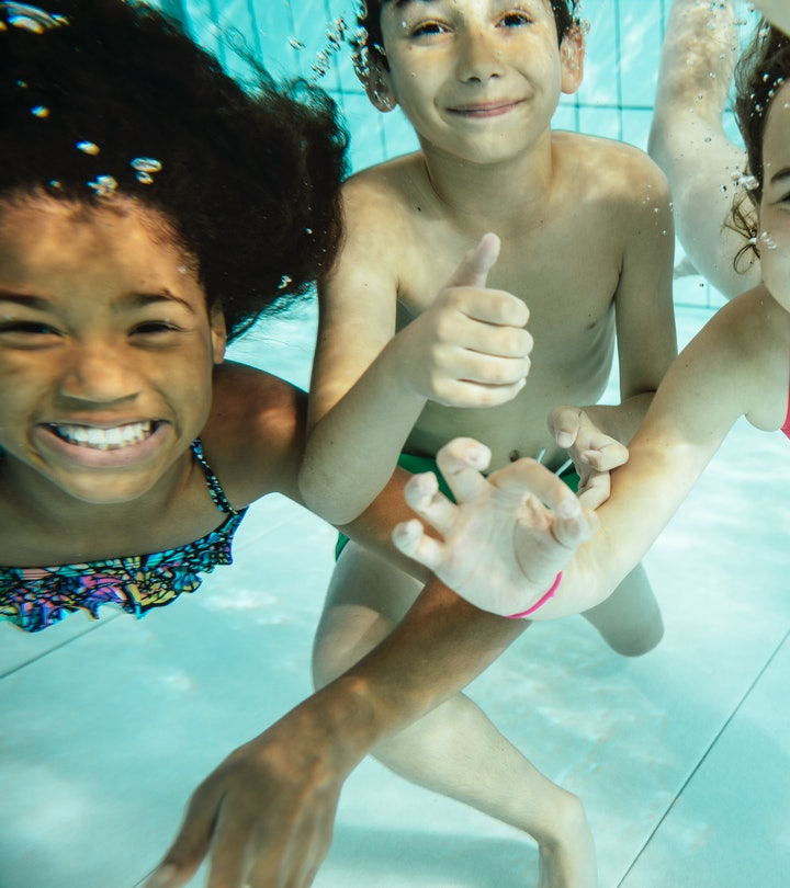 Kids swimming underwater, smiling at camera