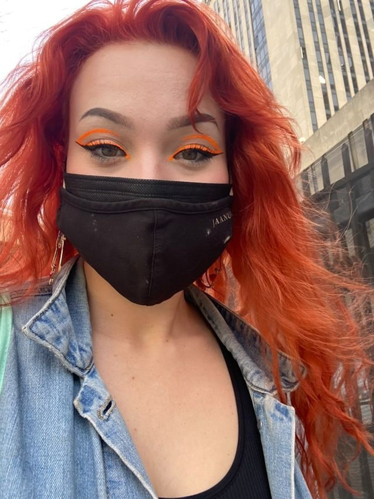 Hayley Adams in a neon orange, graphic eyeliner design using skills she honed for her post-pandemic ...