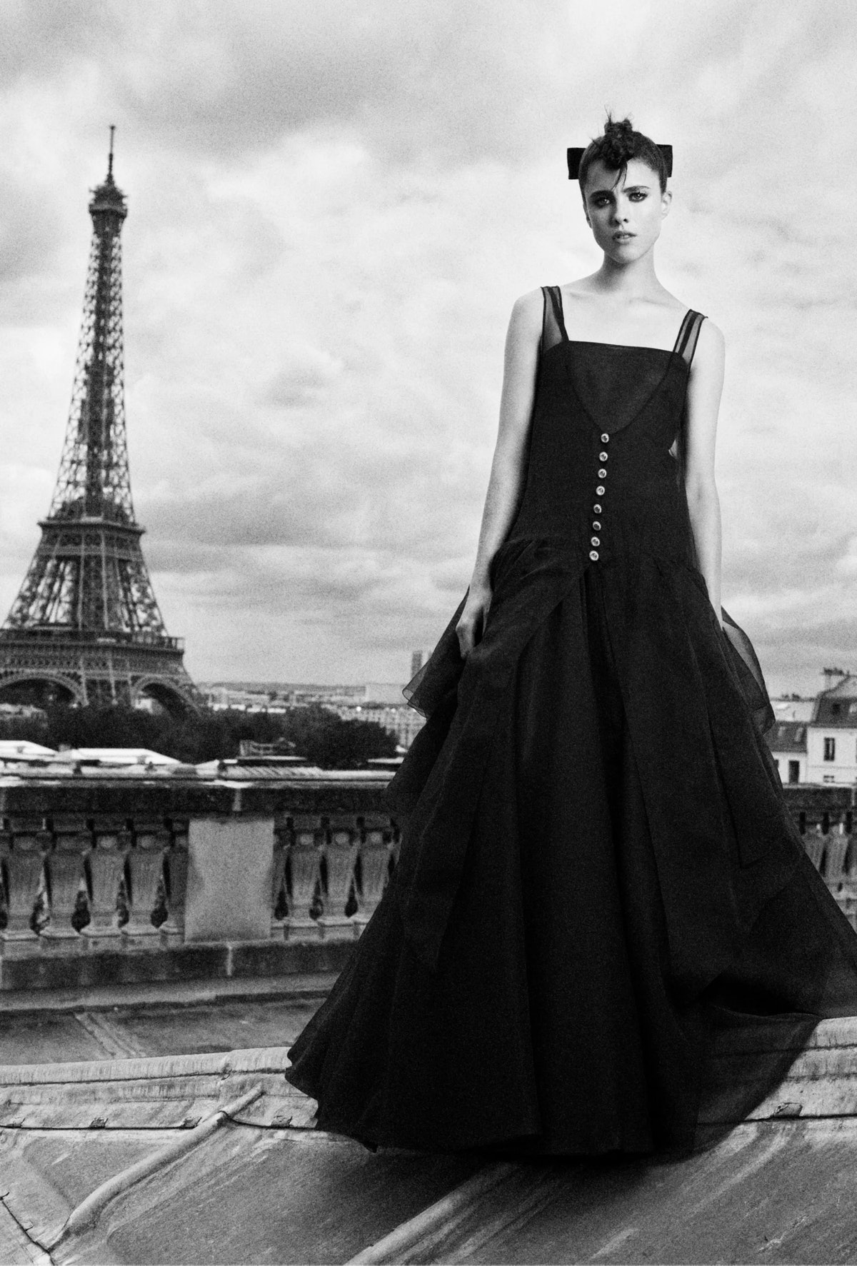 Margaret Qualley, wearing Chanel couture, standing in front of the Eiffel Tower