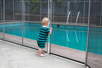 Baby standing in front of gate separating him from a pool