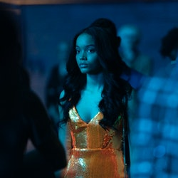 A character from Gossip Girl standing in a dark club. Her dress is orange and looks neon in the blue...