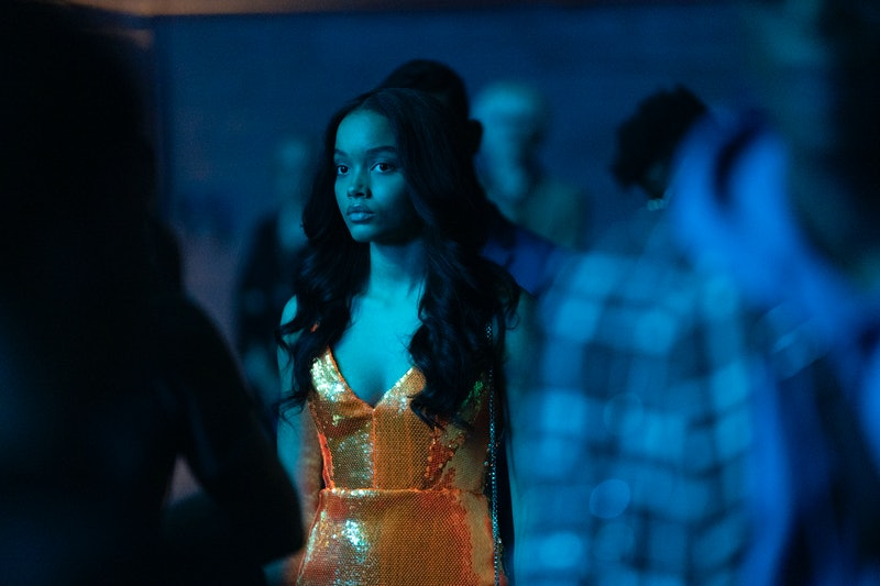 A character from Gossip Girl standing in a dark club. Her dress is orange and looks neon in the blue light.