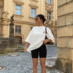Influencer THANYAW wears black bike shorts in 2021, paired with an oversize white tee and chunky New Balance sneakers.
