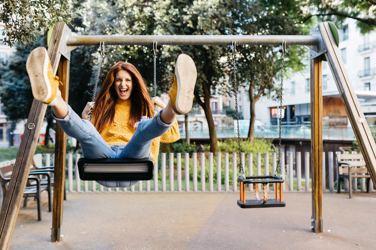 Young Cancer woman smiling while on a swing.