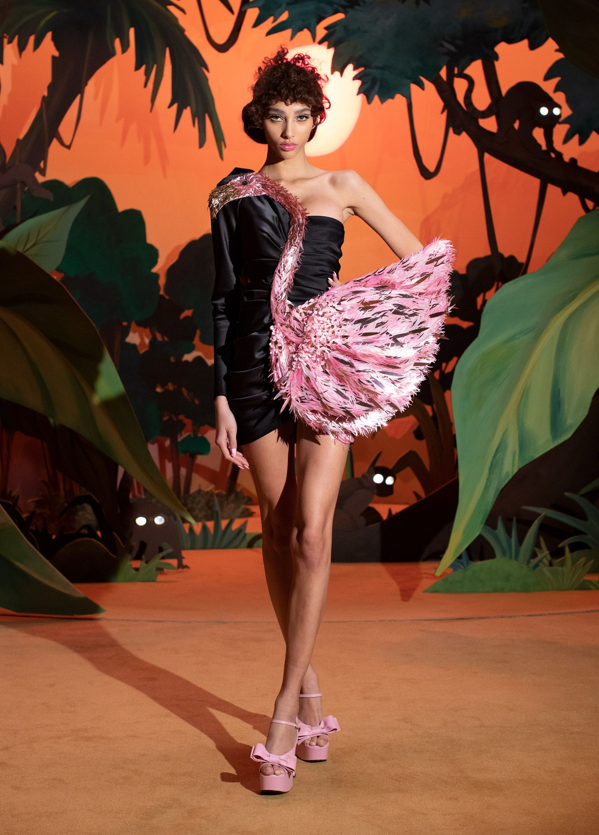A model in the Moschino fall 2021 shoe wearing a flamingo dress with Y2K, bow-top heels