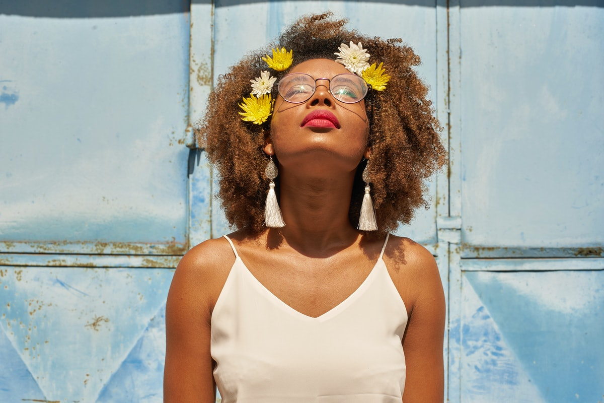 Young woman with red lips wearing glasses and flowers in her hair looking up during the July 2021 ne...