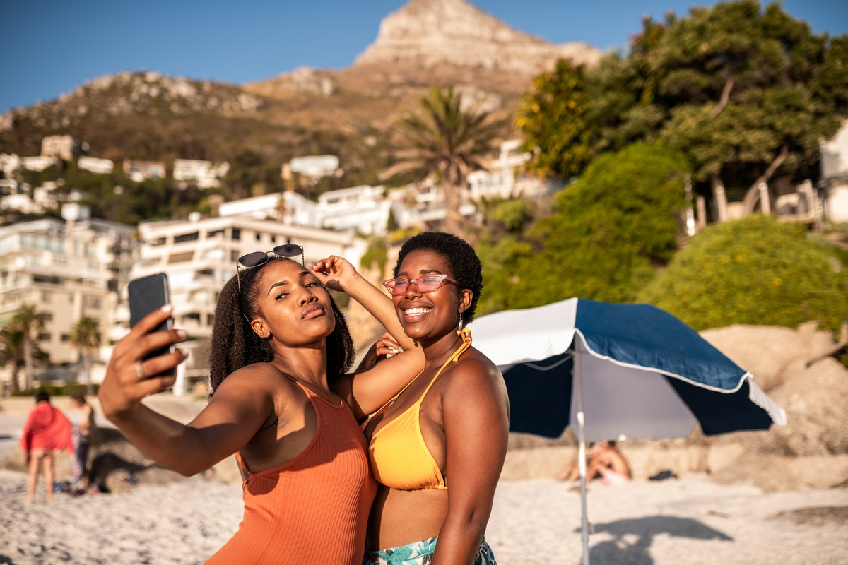 2 friends taking a selfie at the beach in the summer sun before posting a pic on Instagram with a fun caption.