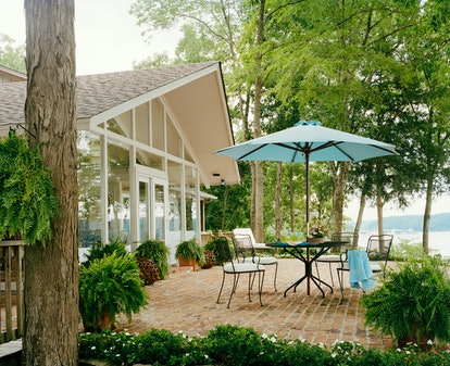 backyard patio with small round dining table and blue umbrella