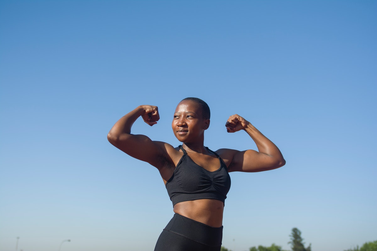 Strong woman flexing her muscles on her 25th birthday, after turning 25.