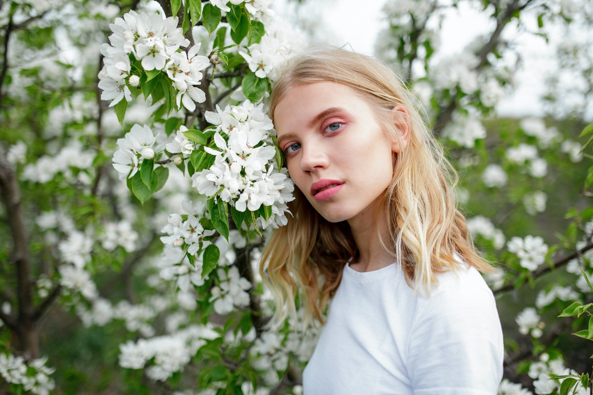 Young woman with a stellium in her birth chart, according to astrology, surrounded by white blossoms.
