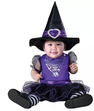 baby dressed in a black and purple witch outfit for Halloween