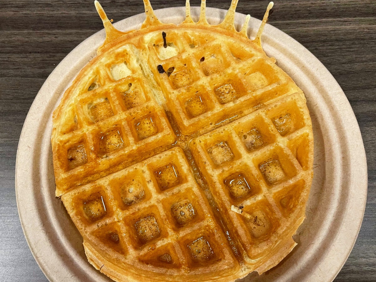 A golden brown waffle on a paper plate.