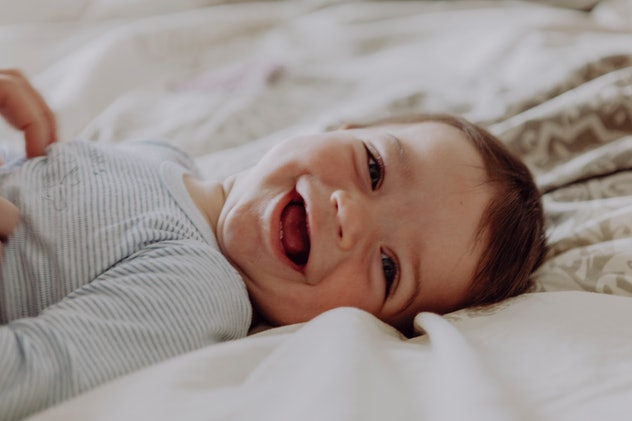 happy baby lying in bed, laughing