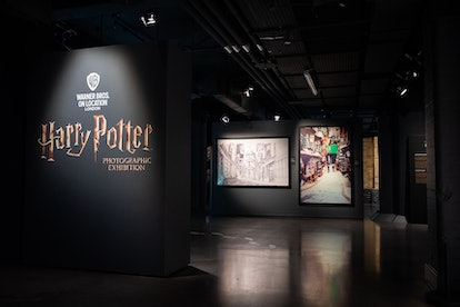 a picture of an exhibition room where photos of diagon alley are displayed against a black backdrop