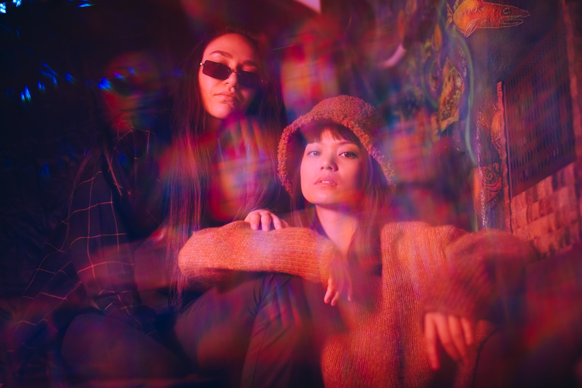 Multiple exposure of young female friends sitting together at illuminated restaurant wondering about...