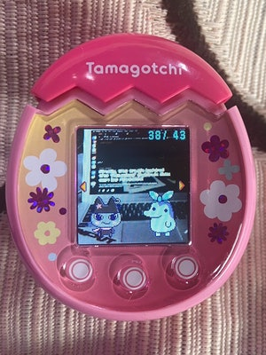 Two Tamagotchi characters are pictured standing on a laptop