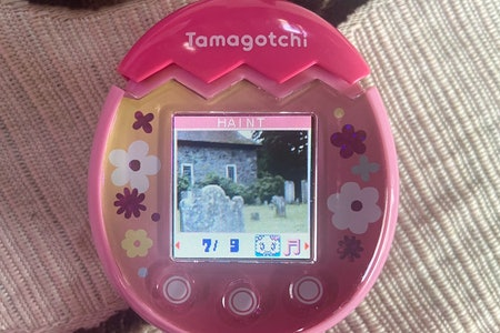 A graveyard with a stone house in the background is pictured on the screen of Tamagotchi Pix