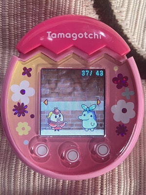 Two Tamagotchi characters are pictured standing in front of a brick wall