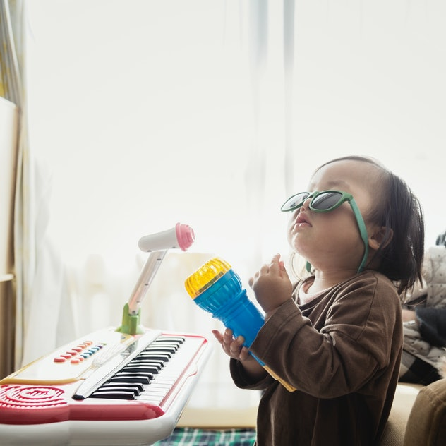 baby rocking out in sunglasses with toy microphone and keyboard