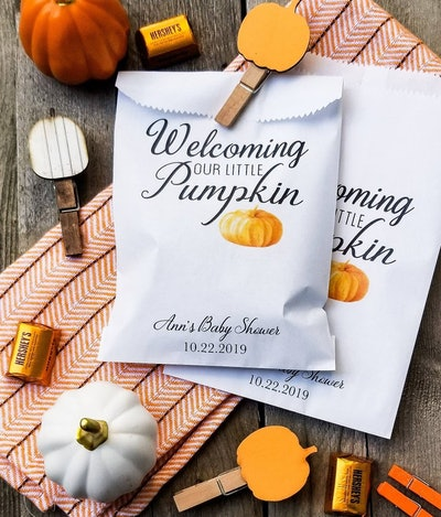 """Close up of filled baby shower favor bag that says """"welcoming our little pumpkin"""""""