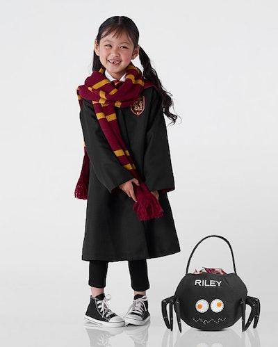 Little girl wearing Harry Potter costume for Halloween