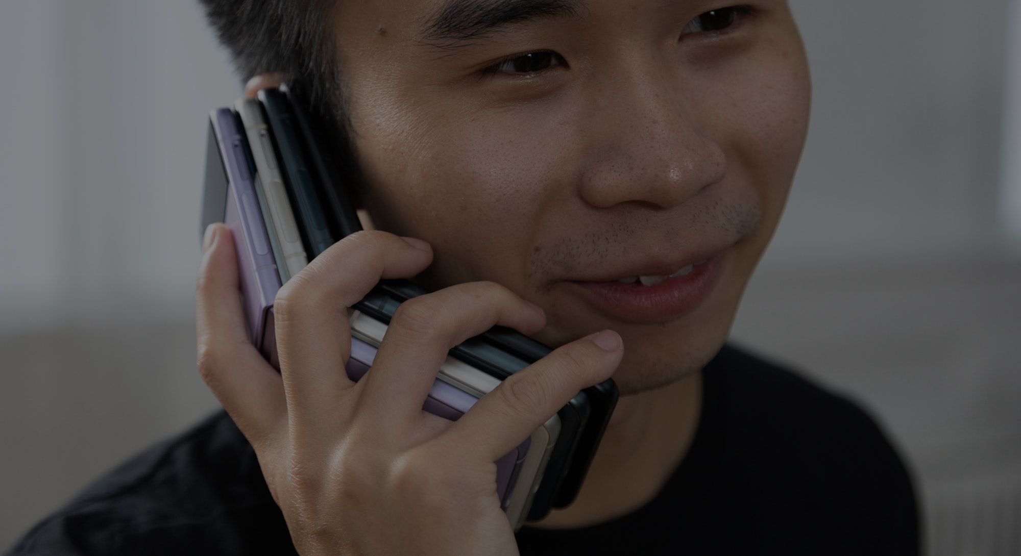Holding a stack of four Samsung Galaxy Z Flip 3 foldable Android smartphones