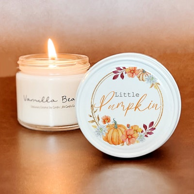 """Lit candle with jar topper propped up on it that reads """"Little Pumpkin"""""""