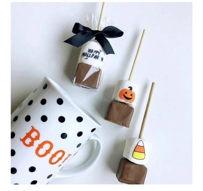 Coffee cup with Jack-o-lantern next to three hot chocolate sticks with Halloween-themed marshmallows
