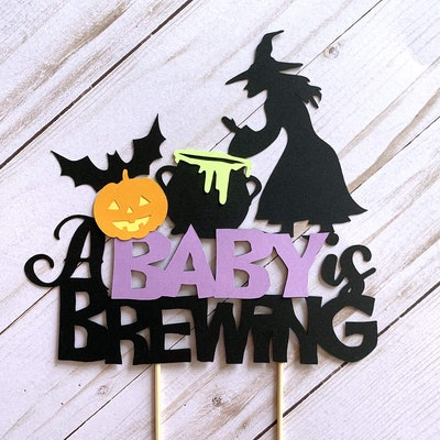 """Cake topper with witch, cauldron, jack-o-lantern, and bat that says """"A Baby Is Brewing"""""""