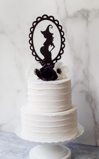 White cake with black cake topper of a pregnant witch silhouette