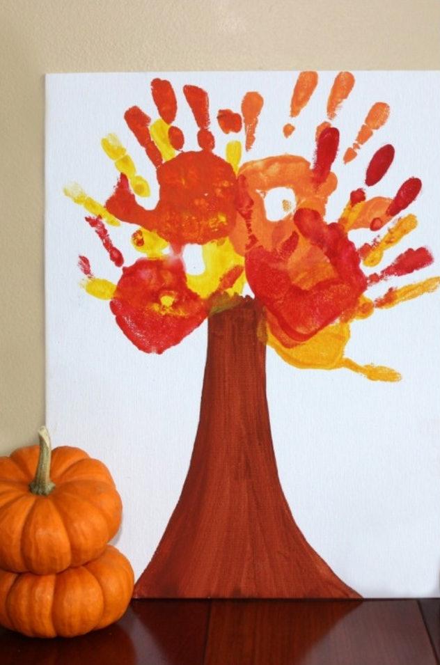 A fall-themed tree is one Halloween handprint art idea.