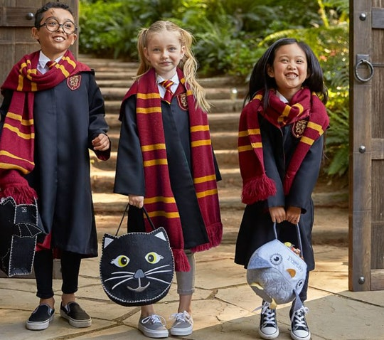 """Three kids standing together, wearing """"Harry Potter"""" costumes and holding Halloween buckets"""