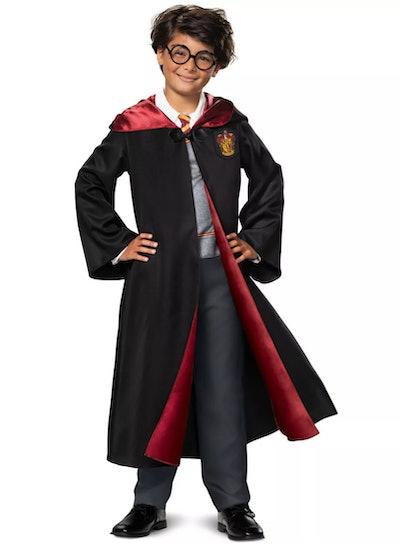 Little boy, posing, wearing Harry Potter costume.