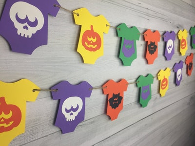 Garland with colorful baby onesies with Halloween pictures on them (skull, pumpkin, etc.)