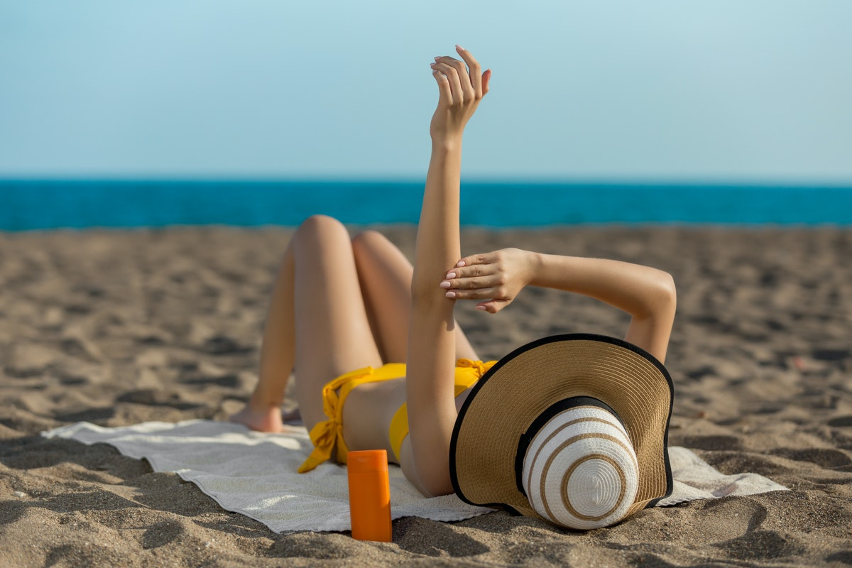 Woman on beach using sunscreen