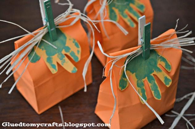 Handprint pumpkin bags is a Halloween handprint art idea to make.