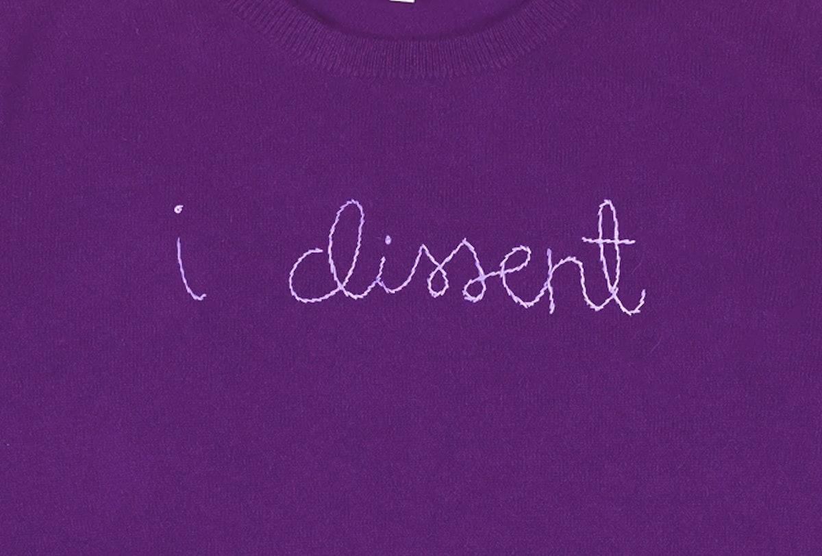 "purple sweater with ""i dissent"" stitching"