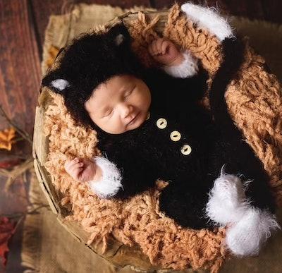 Newborn wearing black cat costume.