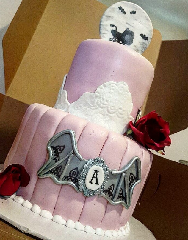 Two tiered pink cake with a silver bat, and a spooky topper with a moon, bats, and baby carriage