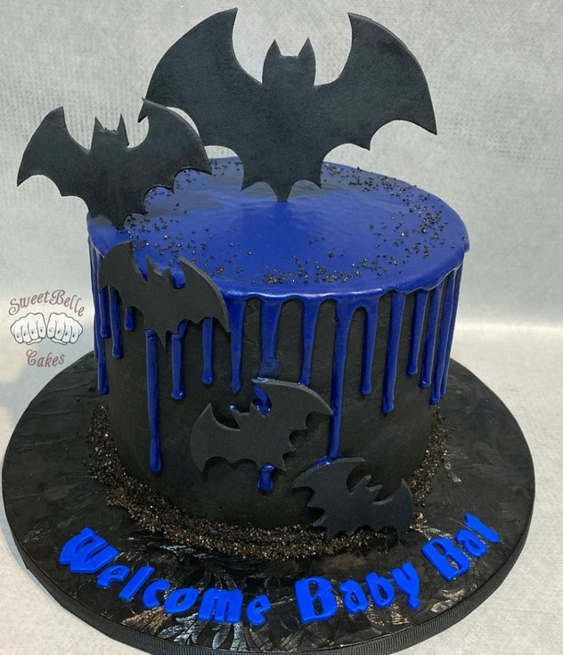 """Black cake with blue icing, black bats, and """"welcome baby bat"""" written in blue"""