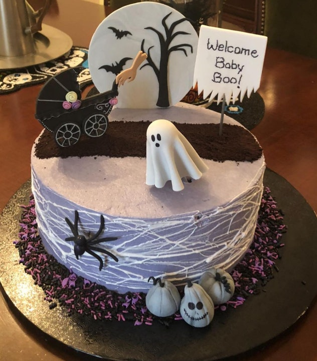 Halloween-themed baby shower cake with carriage, ghost, full moon, spiders and spider webs
