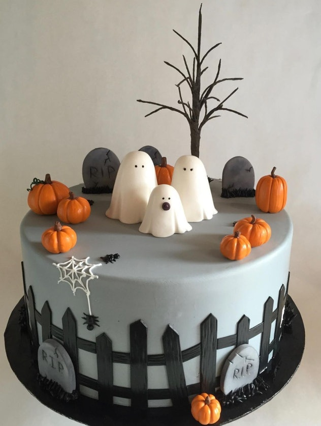 Single layer cake, grey with headstones and black picket fence all around, topped with ghosts and pu...