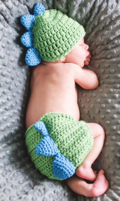 Newborn wearing a dinosaur costume
