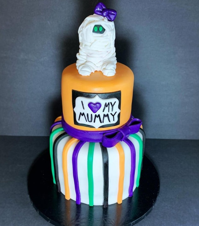 Two tiered cake with baby mummy topper; decorated in Halloween colors orange, black, green, and purp...